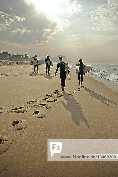 Rear view of friends carrying surfboards while walking on sand at beach