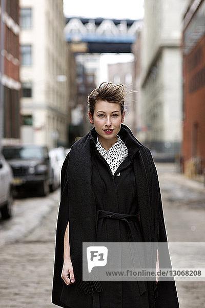 Porträt einer Geschäftsfrau  die auf der Straße vor Gebäuden steht