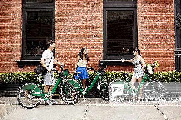 Freunde mit Fahrrad unterhalten sich im Stehen auf dem Bürgersteig-Café