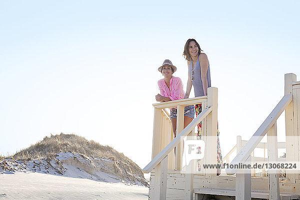 Freunde schauen weg  während sie am Pier gegen den klaren Himmel stehen