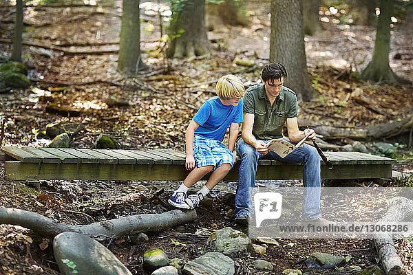 Teacher showing book to boy while sitting on footbridge