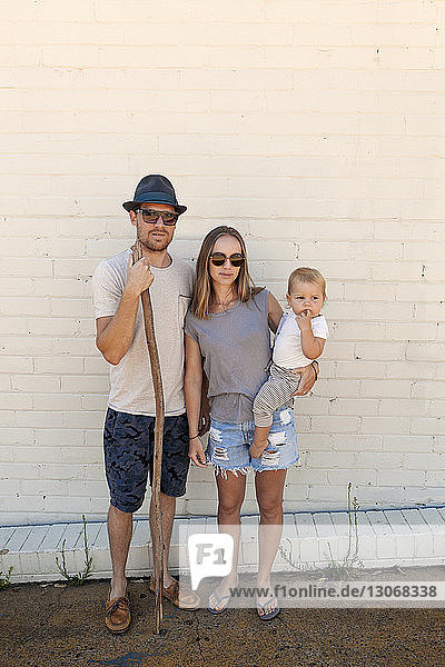 Portrait of family standing against brick wall