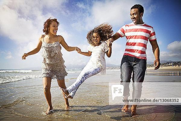 Eltern schwingen Mädchen beim Uferspaziergang am Strand