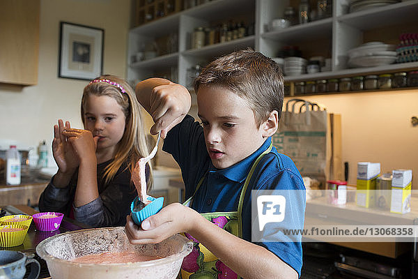 Girl looking at brother filling cupcake holders in kitchen