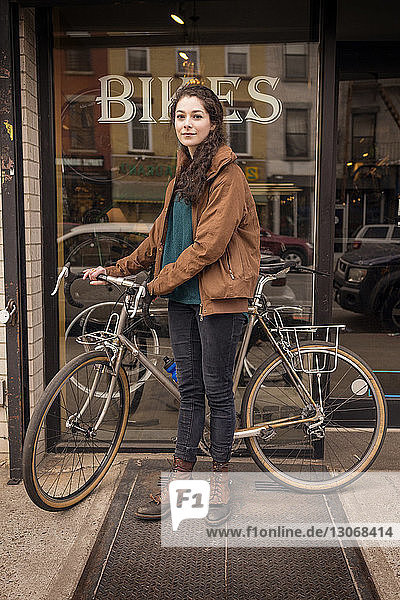 Portrait of woman with bicycle standing against bicycle shop