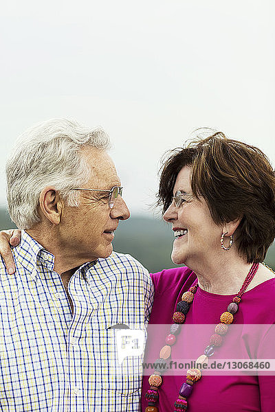 Senior couple with arm around standing against sky
