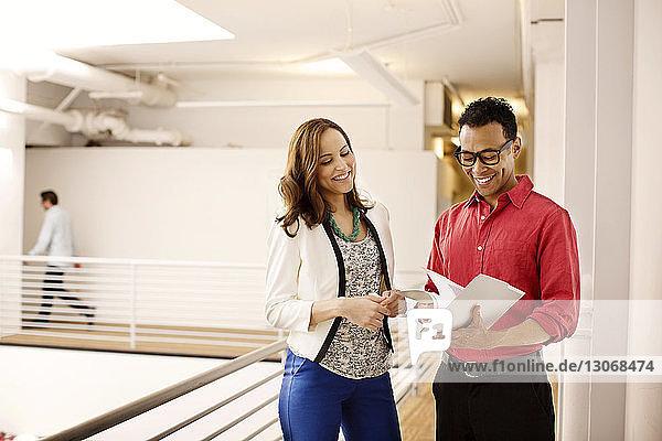 Lächelnde Geschäftsleute stehen im Korridor