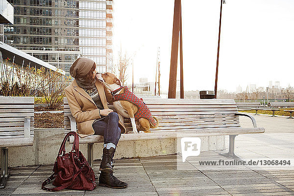 Woman kissing dog while sitting on bench against office building