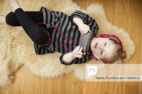 Schrägansicht eines Mädchens  das zu Hause auf dem Teppich liegend per Handy Musik hört