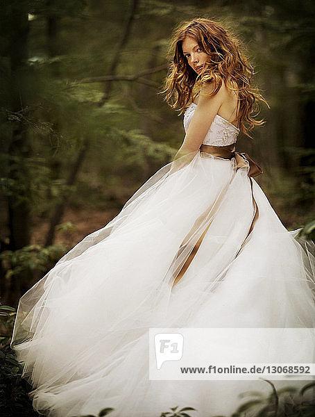 Porträt einer selbstbewussten Frau im Wald stehend