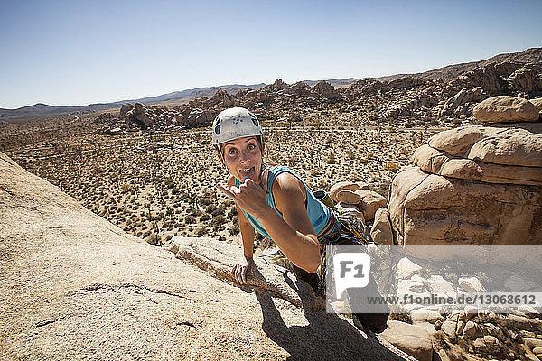 Porträt einer glücklichen Frau  die beim Erklimmen einer Felsformation gegen den Himmel gestikuliert