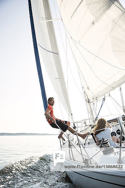 Couple enjoying drink while traveling in yacht