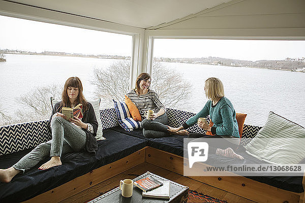 High angle view of friends relaxing against glass windows at home