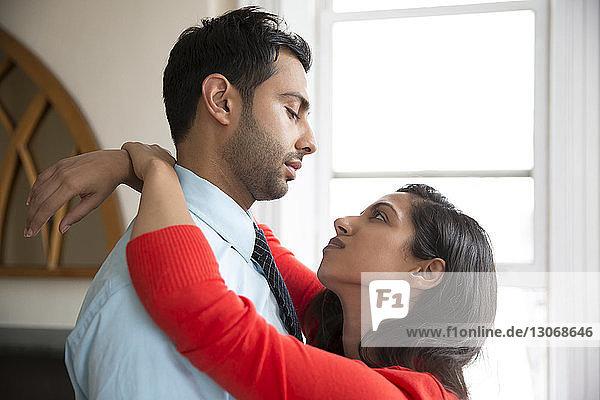 Paar umarmt sich im Stehen zu Hause
