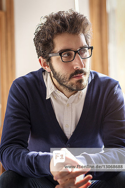 Thoughtful man looking away while sitting at home