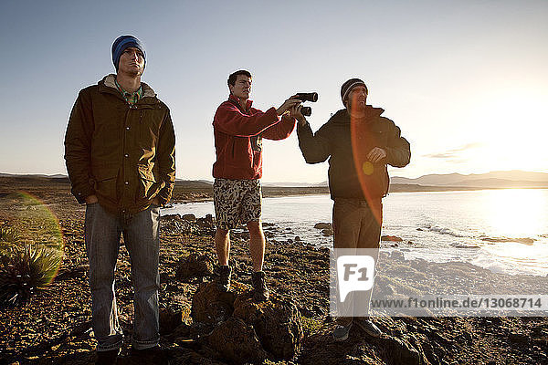 Freunde stehen an felsiger Meeresküste gegen den Himmel