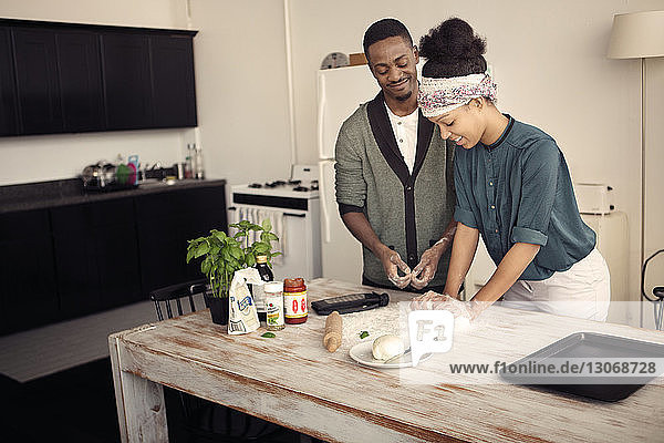 Smiling man assisting woman in kneading dough at kitchen table