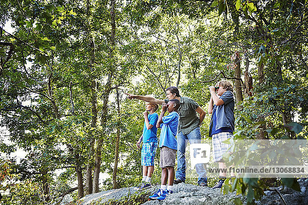 Teacher explaining students while standing on rocks in forest during field trip