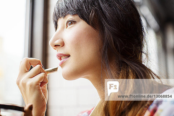 Frau schaut weg  während sie Lippenstift aufträgt