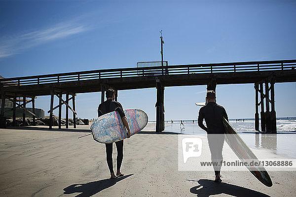 Rückansicht von Männern mit Surfbrettern am Strand