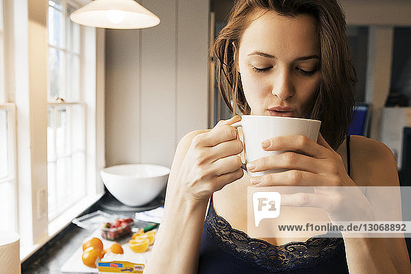Woman drinking coffee while standing in kitchen
