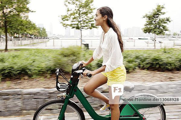 Glückliche Frau fährt Fahrrad auf der Straße in der Stadt