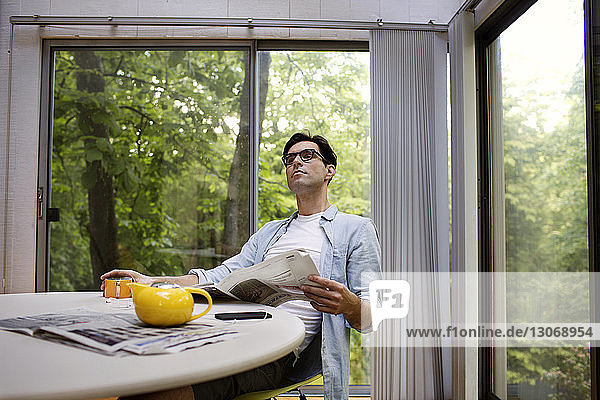 Thoughtful man holding newspaper while having tea at table against window