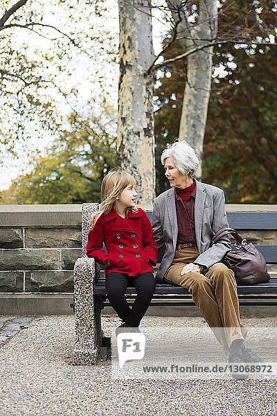 Woman looking at granddaughter while sitting on bench at park