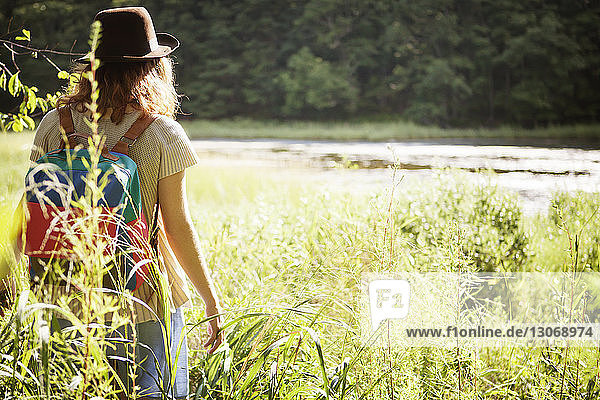 Rückansicht einer im Wald stehenden Frau