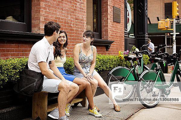 Freunde mit Fahrrad unterhalten sich  während sie auf einer Bank im Straßencafé sitzen