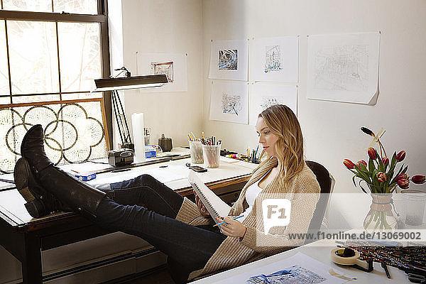 Frau hält Notizblock und Stift  während sie im Kunstatelier sitzt