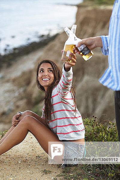 Ein paar Bierflaschen beim Entspannen auf dem Feld anstoßen