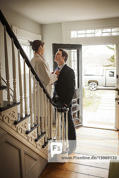 Woman adjusting man's tie while standing on staircase at home