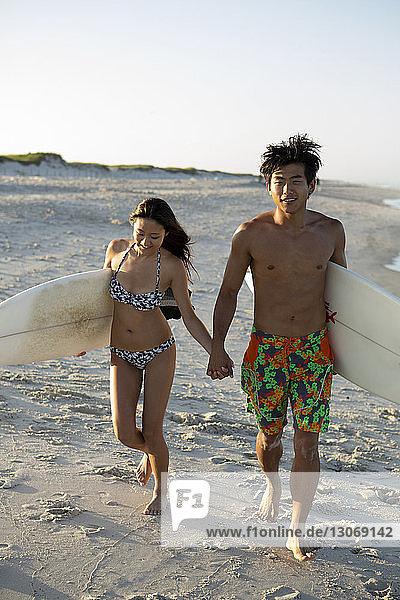 Paar mit Surfbrettern  die sich beim Strandspaziergang am Ufer an den Händen halten
