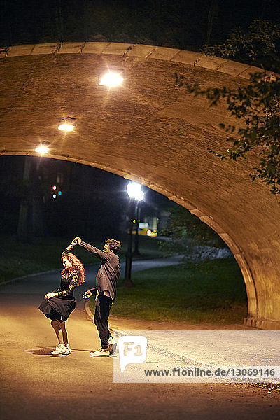 Happy couple dancing on street at night