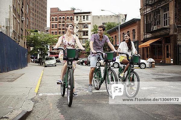 Glückliche Freunde fahren Fahrrad auf der Straße