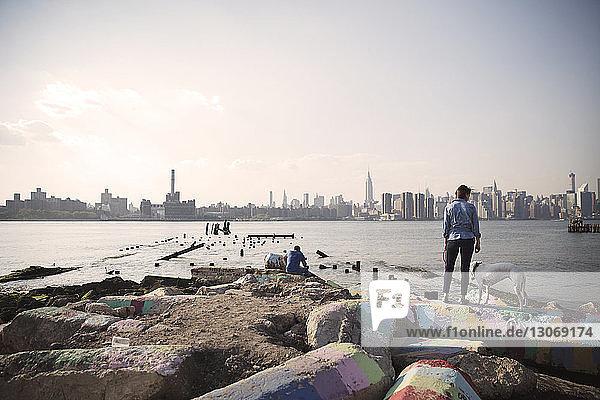Frau steht mit Hund auf Buhnen am Meer gegen Stadt