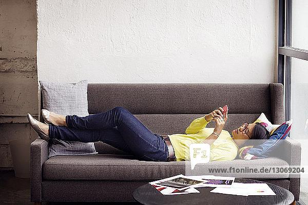 Seitenansicht einer Frau  die ein Smartphone benutzt  während sie im Büro auf dem Sofa liegt