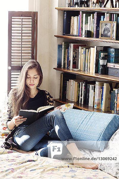 Frau lernt  während sie am Fenster am Bett sitzt