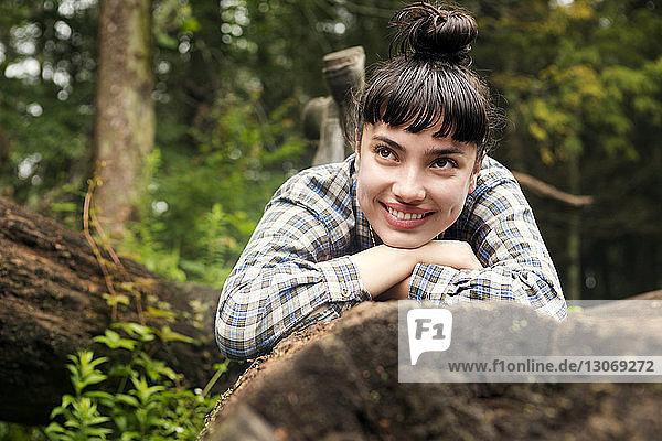 Glückliche Frau schaut weg  während sie auf einem Baumstamm im Wald liegt