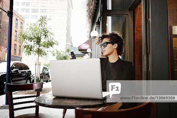 Frau mit Laptop-Computer sitzt im Straßencafé