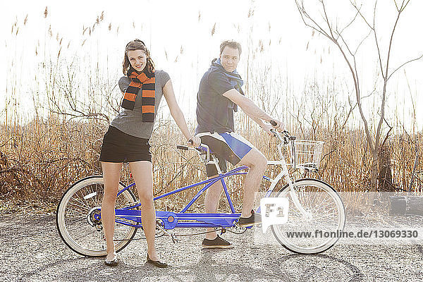 Couple standing with tandem bicycle against clear sky