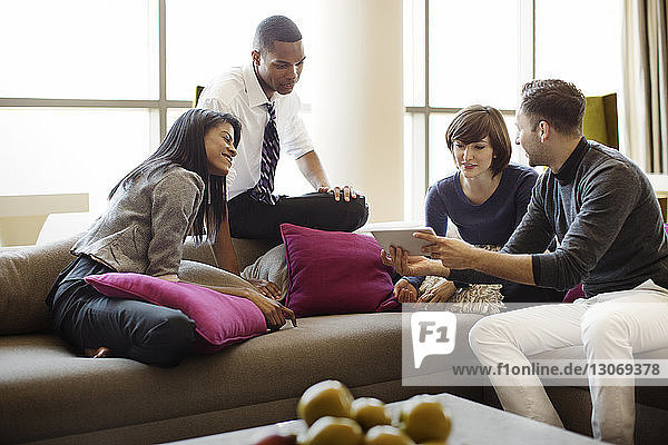 Man showing tablet computer to colleagues talking while sitting on sofa