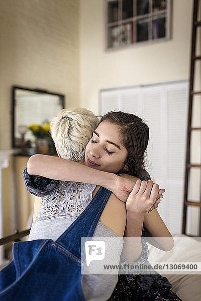 Freundinnen umarmen sich  während sie zu Hause auf dem Bett sitzen