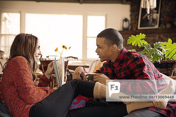 Frau zeigt ihrem Freund ein Buch  während sie sich zu Hause auf dem Sofa ausruht
