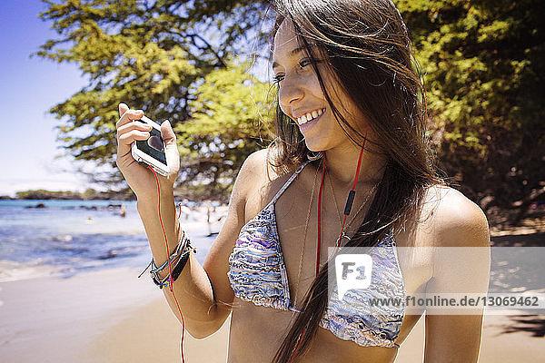 Glückliche Frau  die am Strand stehend mit ihrem Handy Musik hört