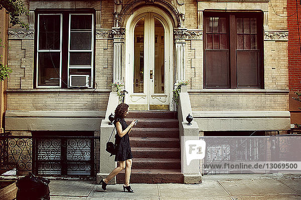 Side view of woman walking against building
