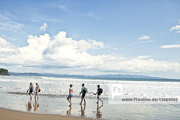 Freunde gehen am Strand gegen den Himmel