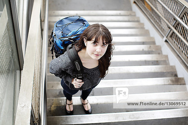 Portrait of woman standing on stairs at railroad station