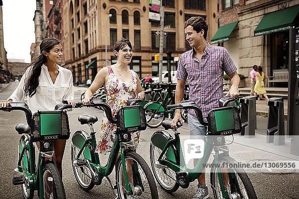 Freunde unterhalten sich beim Gehen auf der Straße mit Fahrrädern